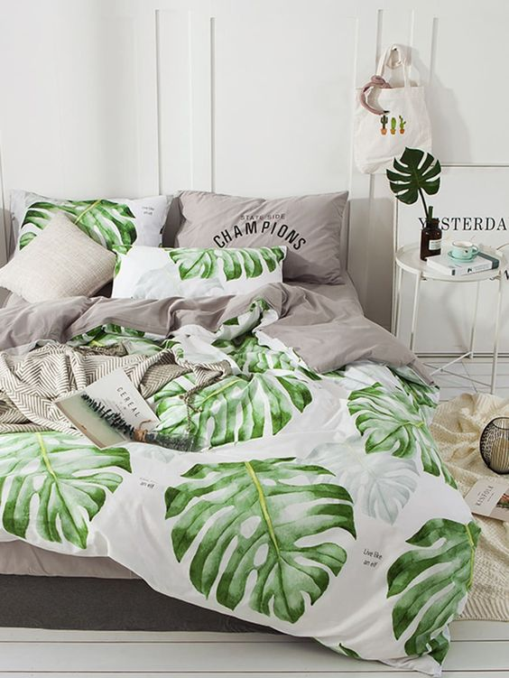 a modern tropical bedroom done all neutral, with tropical leaves and with grey and tropical leaf print bedding