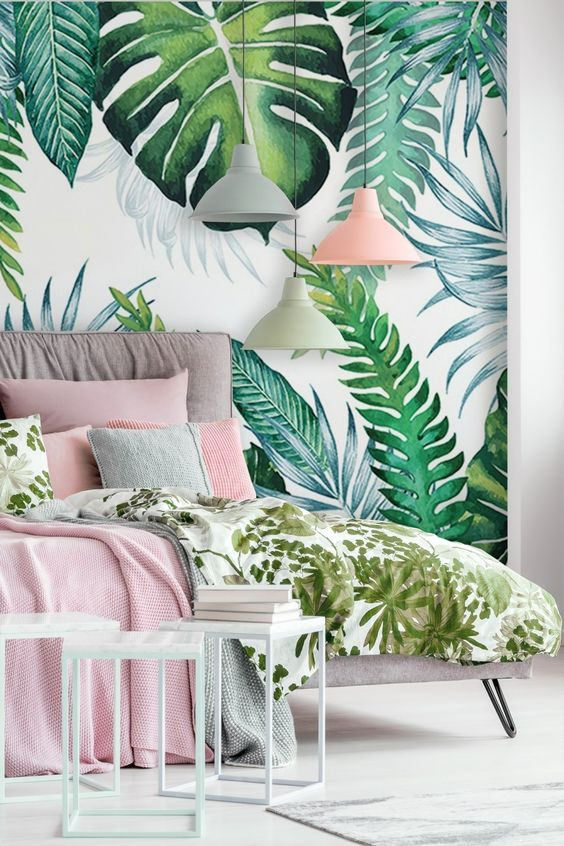 a modern tropical bedroom with a tropical leaf wall, an upholstered bed, some side tables and cool pink and green bedding