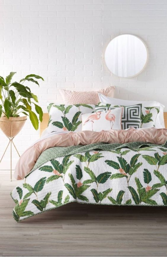 a modern tropical bedroom with a white brick wall, printed bedding with leaves and flamingos and potted plants