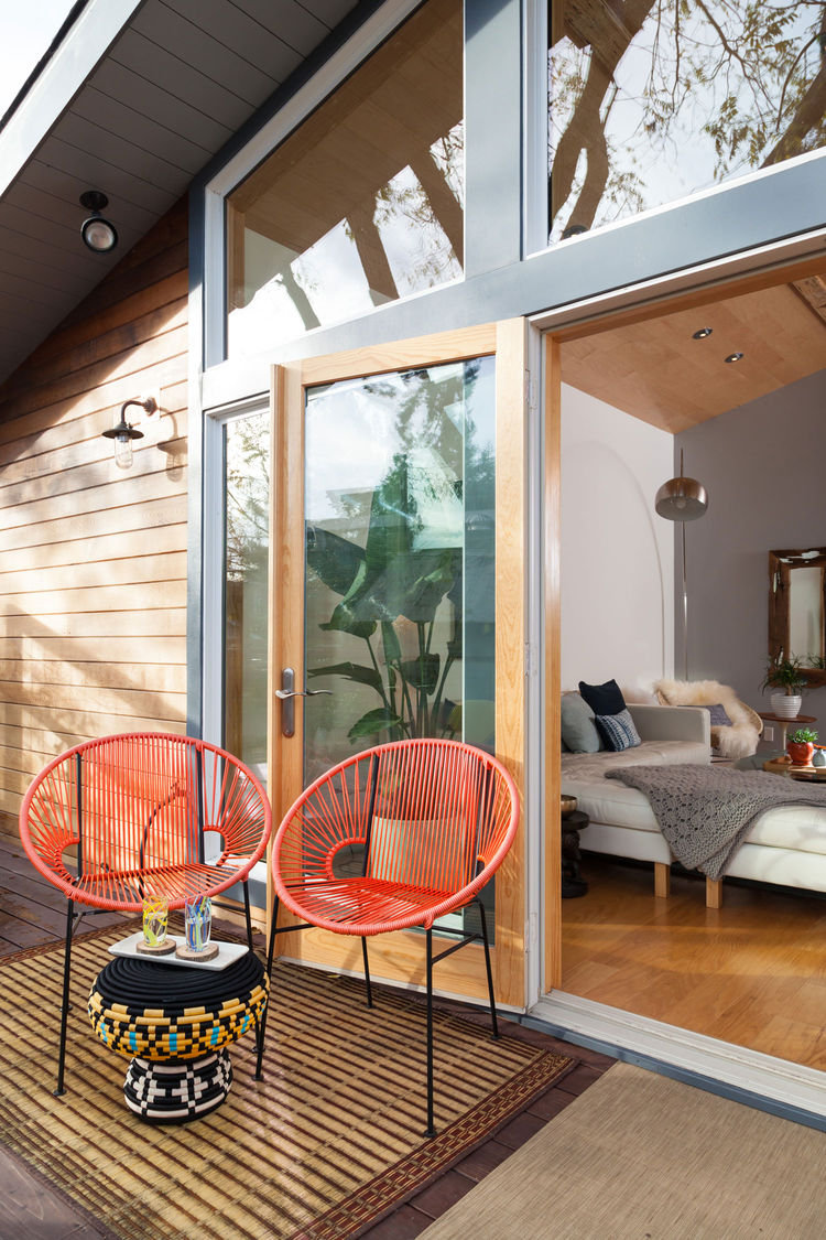 a modern tropical porch with red woven chairs, a bright side table and a jute rug for a bold touch on your porch
