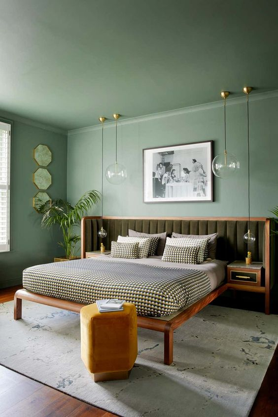 a monochromatic bedroom with a green ceiling and walls, a bed with an extended upholstered green headboard and catchy pendant lamps
