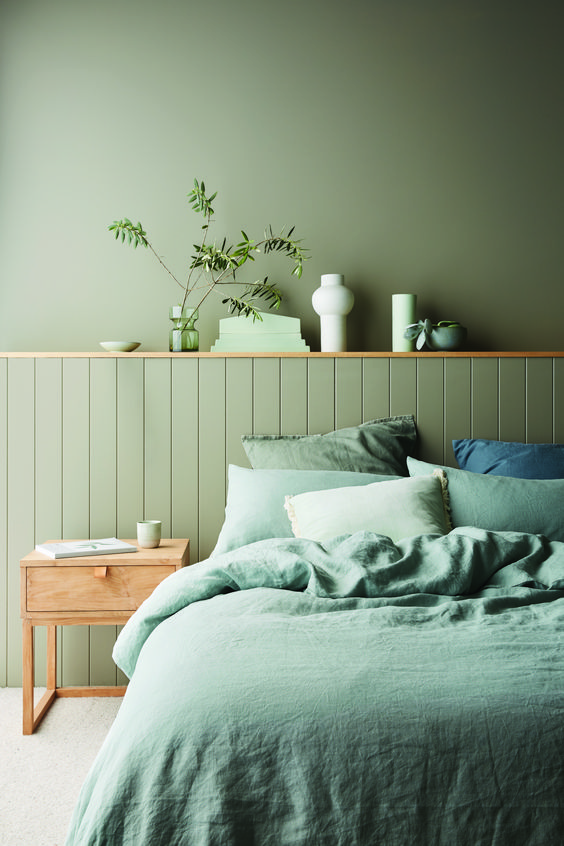 a monochromatic green bedroom with matte walls and beadboards, green bedding and touches of natural wood