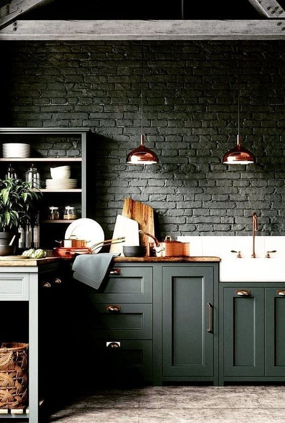 a moody hunter green kitchen with brick walls, stained wooden countertops, copper items for a delicate touch