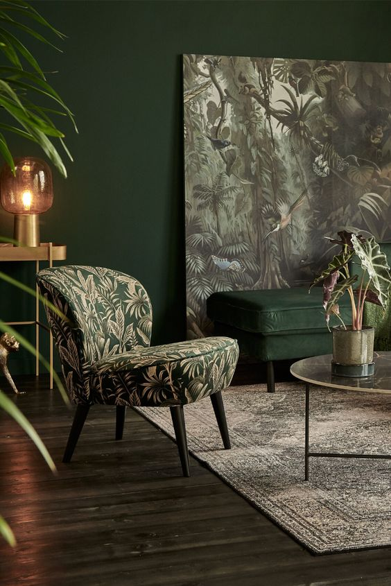 a moody refined living room with hunter green walls, a matching upholstered bench, a moody artwork and a chair plus touches of gold
