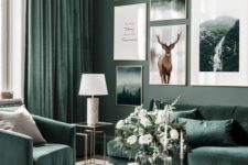 a nature-inspired living room with grey green walls, hunter green furniture and matching curtains and a large gallery wall
