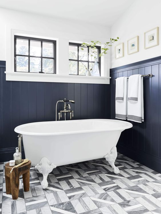 a navy bathroom clad with beadboards, with grey tiles, a white tub in vintage style and a couple of windows