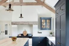 a navy kitchen with a white backsplash, countertops, a large island with a wooden countertop and wooden beams