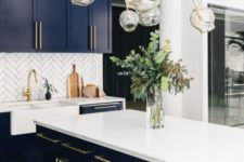 a navy kitchen with a white tile backsplash, white countertops and a statement gold and bubble chandelier