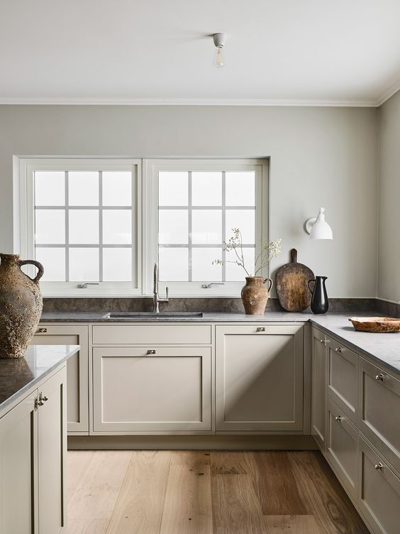 a neutral Nordic kitchen with dove grey cabinets, stone countertops and some stone and wood accessories