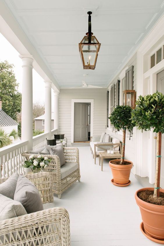 a neutral and welcoming summer porch with neutral wicker furniture, a wooden sofa, potted trees