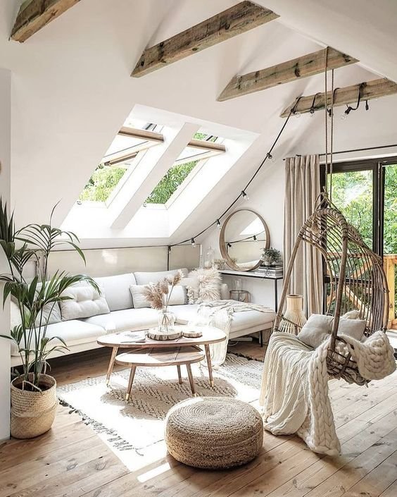 a neutral boho attic living room with skylights, beams, a suspended chair, wooden coffee tables