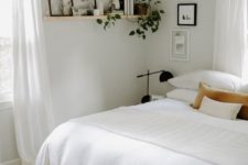 a neutral boho bedroom  wiht a wooden bed, nightstands, black lamps and a woven one, a shelf with books and greenery