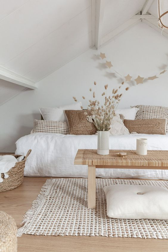 a neutral boho bedroom with a low bed, a woven bench, jute rugs and baskets plus neutral pillows