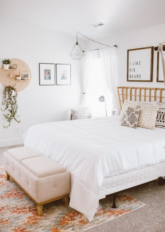 a neutral boho bedroom with a rattan bed, a metal lamp, a pegboard with greenery, a gallery wall and a soft bench