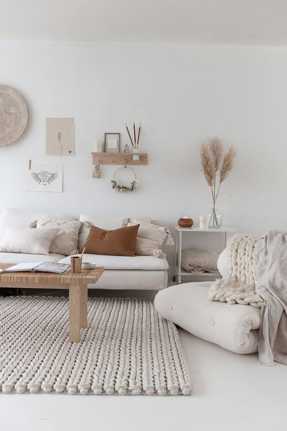 a neutral boho living room with white furniture, a gallery wall, knit items and a woven bench