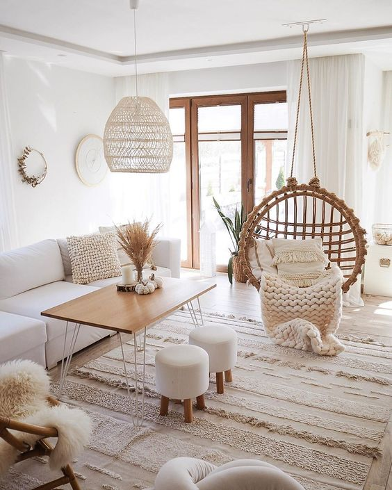 a neutral boho living room with white furniture, a suspended chair, a wooden table and stools