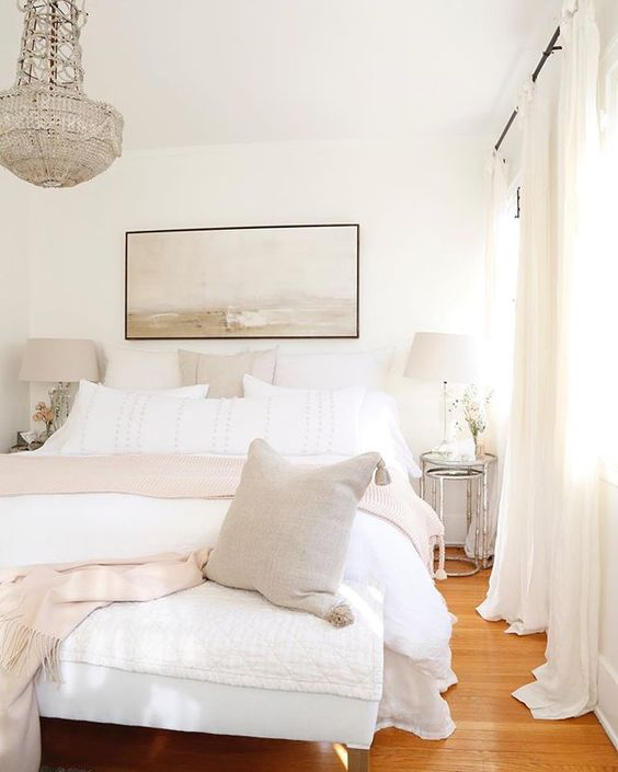 a neutral chic bedroom with a white bed and bench, shiny glass nightstands, lamps and a gorgeous crystal chandelier