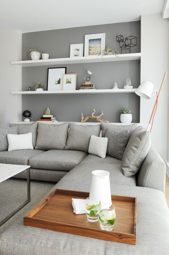 a neutral contemporary living room with a grey sectional, white floating shelves and a marble coffee table