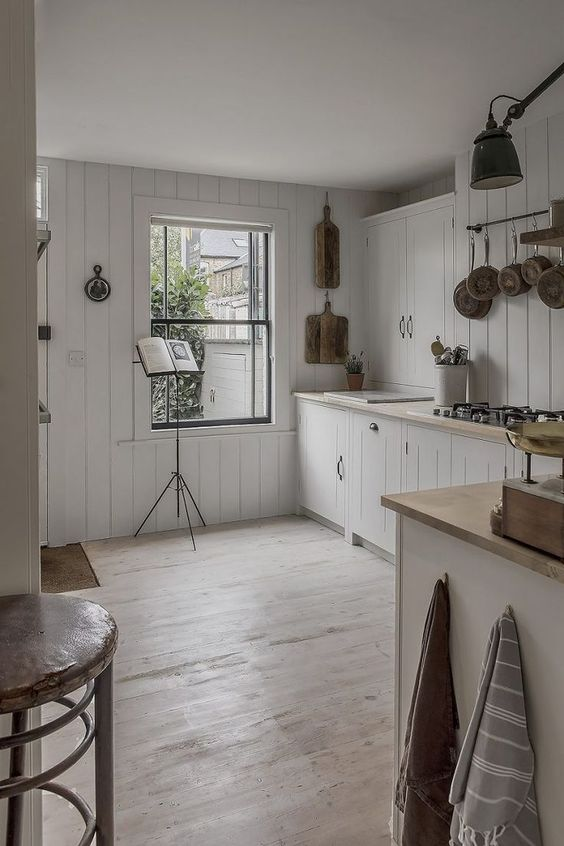 a neutral cottage kitchen with white beadboard, wooden countertops, railings, a large window with much natural light