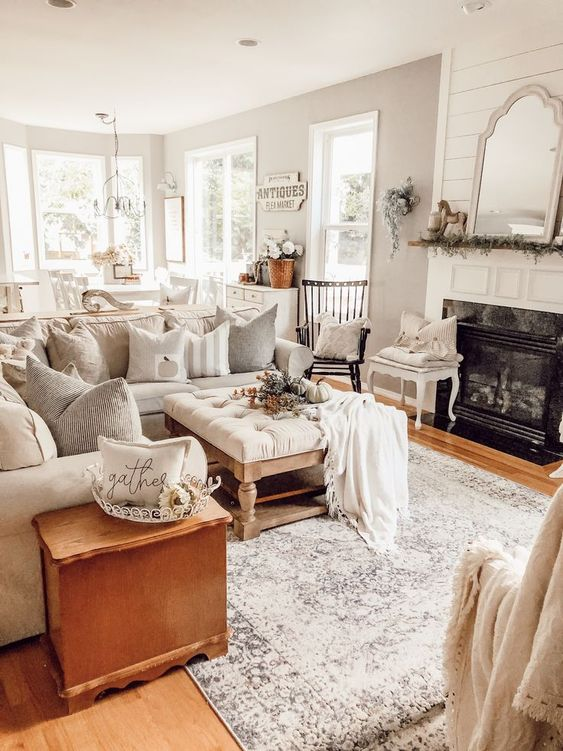 a neutral cottage living room with a built-in fireplace, a neutral sofa, vintage furniture, a white frame mirror
