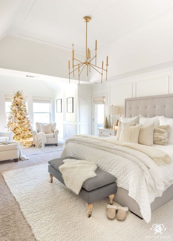a neutral farmhouse bedroom with a grey bed, a grpahite grye bench, white chairs and gold touches