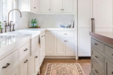 a neutral farmhouse kitchen with white marble tiles, woven shades, a boho rug and a grey kitchen island