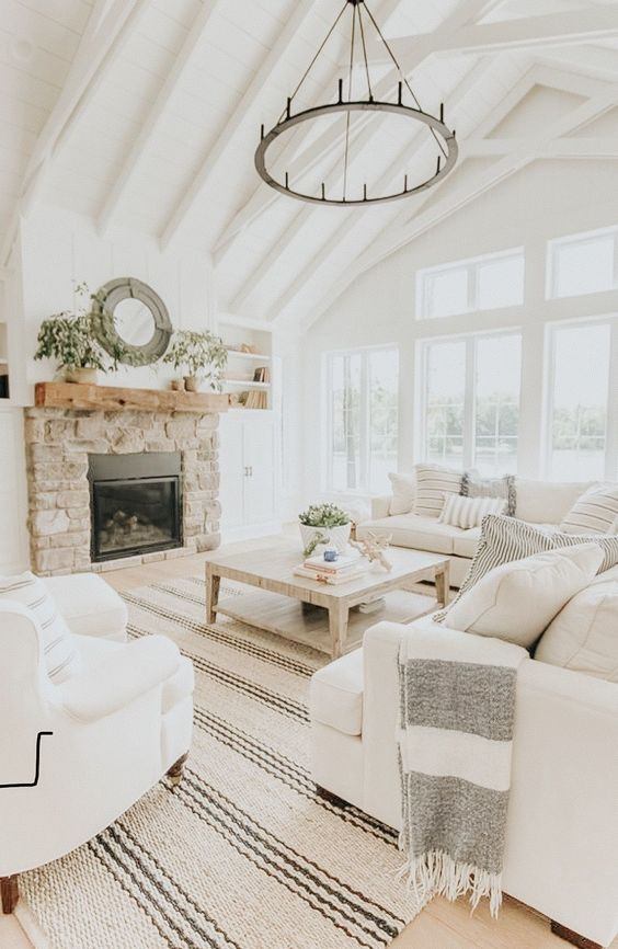 a neutral farmhouse living room with wooden beams, a round chandelier, white furniture, a built-in fireplace in stone
