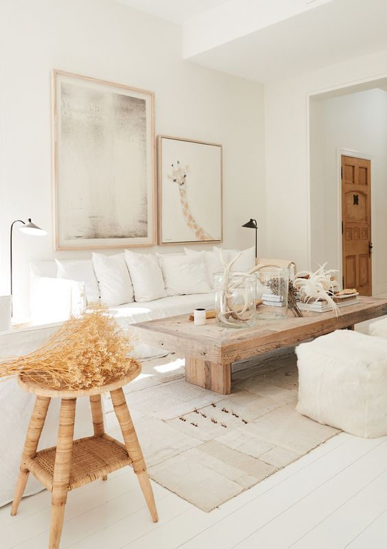 a neutral living room ith white furniture, a wooden table and stool, layered rugs, a gallery wall
