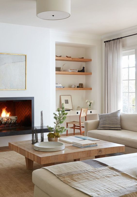 a neutral living room with neutral furniture, a cozy fireplace, a wooden table and a small home office nook