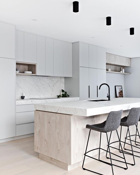 a neutral minimalist kitchen with dove grey cabinets, a white marble backsplash and countertops, a wooden kitchen island and felt stools