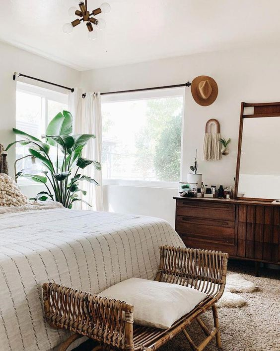 a neutral tropical boho bedroom with a rattan loveseat, wooden furniture and a statement tropical plant