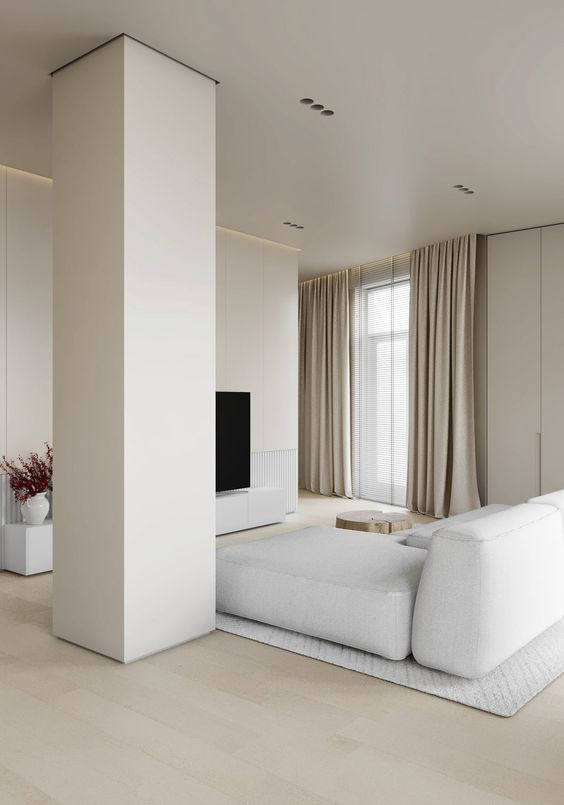 a neutral ultra-minimalist living room with a TV, a white sectional, a pillar and neutral textiles