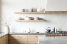 a peaceful contemporary kitchen with white walls, wooden and concrete cabinets and a white tile backsplash