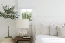 a peaceful natural bedroom with a white bed, a wooden bench and nightstands, a catchy beaded lamp and a statement plant