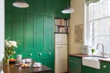 a pretty emerald kitchen with dark stained wooden countertops, pendant lamps and printed shades