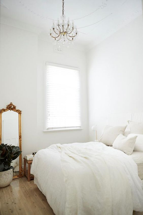 a pure white bedroom with a bed, nightstands and lamps, a wooden bench, a vintage mirror and a chic crystal chandelier