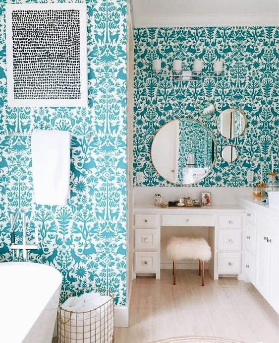 a quirky bathroom with walls covered with flora and fauna turquoise wallpaper, white furniture and appliances looks fun