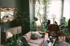 a quirky living room with hunter grene walls, a matching sofa, lots of potted greenery and touches of animal prints