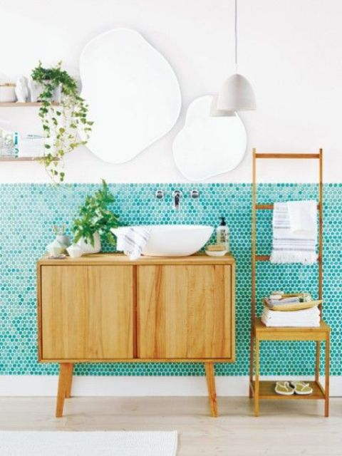 a quirky modern bathroom with turquoise penny tiles, wooden furniture, uniquely shaped mirrors, open shelving and a pendant lamp