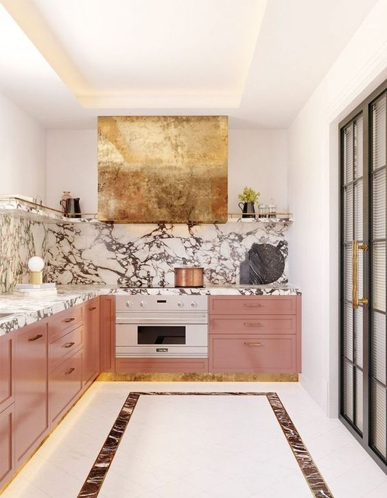 a refined and glam kitchen with pink cabinets, a marble backsplash and countertops, a gold hood looks wow