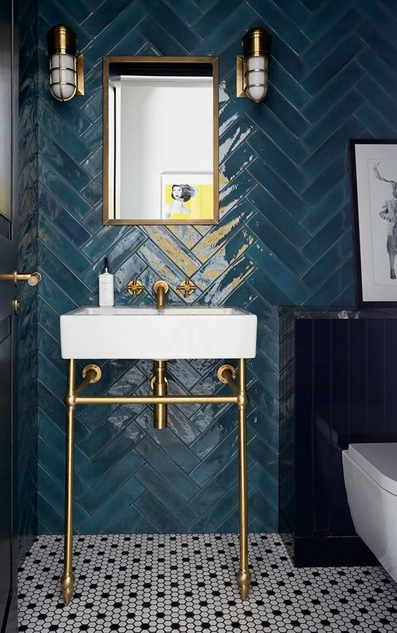a refined bathroom with blue herringbone clad tiles, a chic sink on a stand, sconces and brass touches