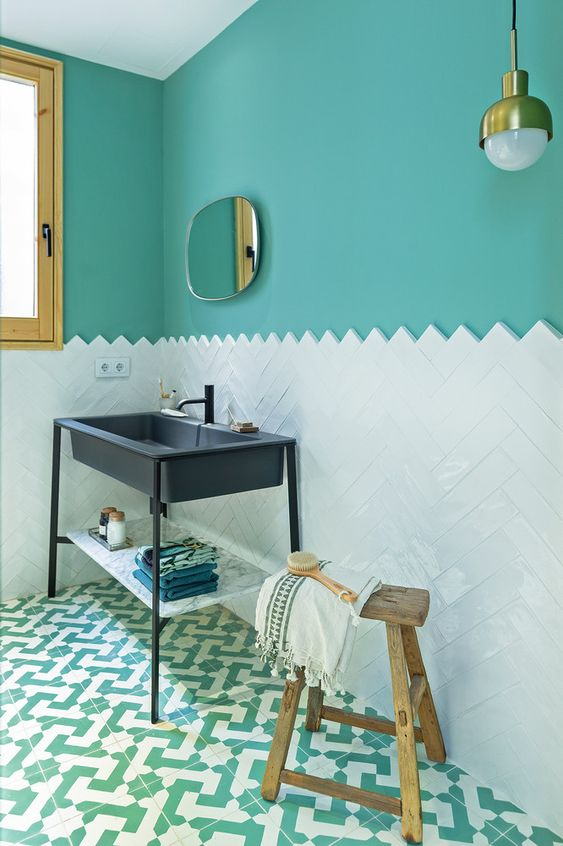 a refined bathroom with turquoise walls, a white tile backsplash, a navy sink on a stand and some touches of wood