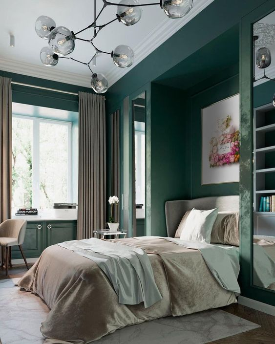 a refined bedroom with dark green walls and storage units, grey and green textiles, a bright artwork and a chandelier