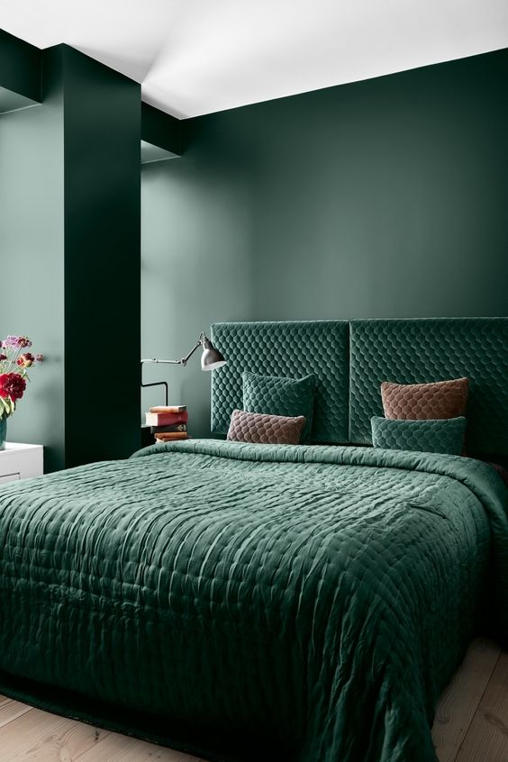 a refined bedroom with matte hunter green walls, a matchin velvet upholstered bed and bedding plus much natural light