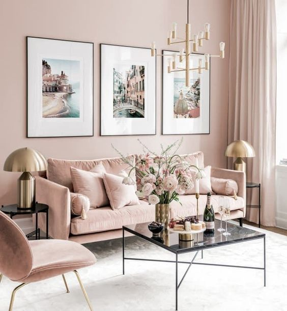 a refined living room with blush walls, blush furniture, a chic gallery wall and touches of gold for glam