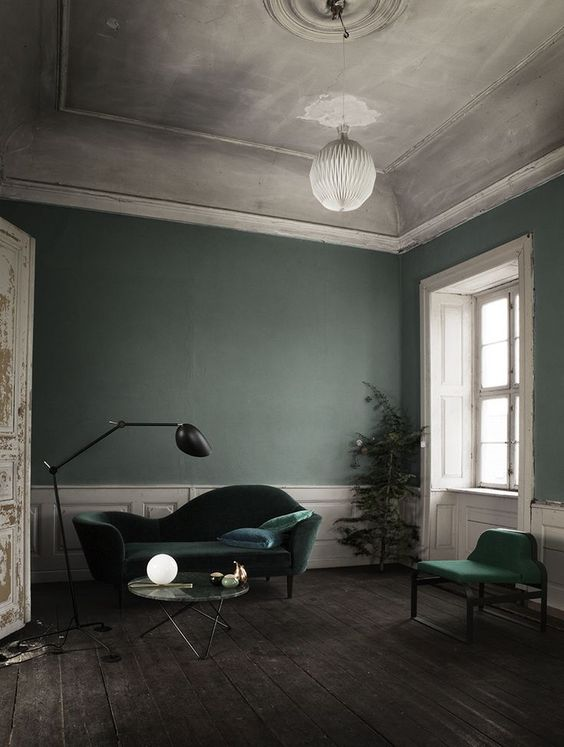 a refined living room with grey green walls, hunter green velvet furniture, white paneling and a chic ceiling