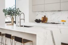 a refined minimalist kitchen with sleek cabinets, tan uppers, a white marble backsplash and countertops, black stools