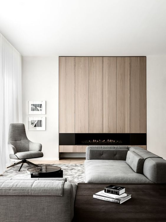 a refined minimalist living room with a wood clad unit with a fireplace, grey furniture and a stylish dark stained table