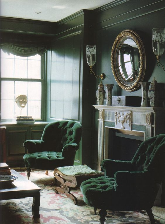 a refined moody living room with dark green walls, hunter green chairs, a clad fireplace, green curtains and touches of gold