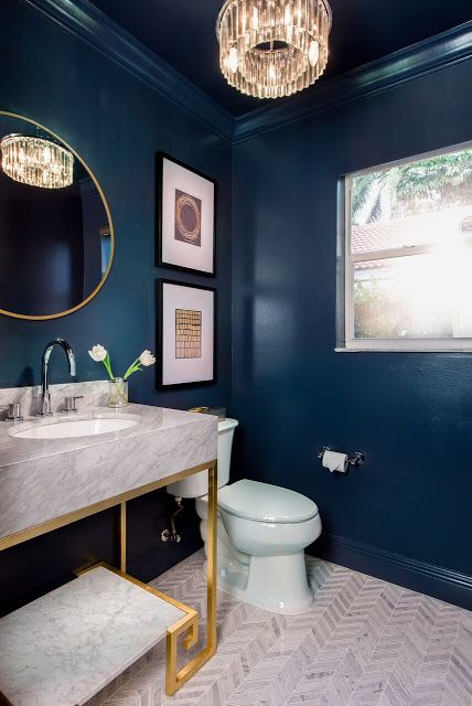 a refined navy powder room with a marble vanity, a crystal chandelier, gold touches and a neutral tile floor